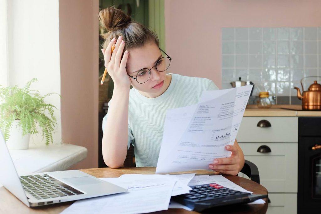 Stressad kvinna framför dator med faktura